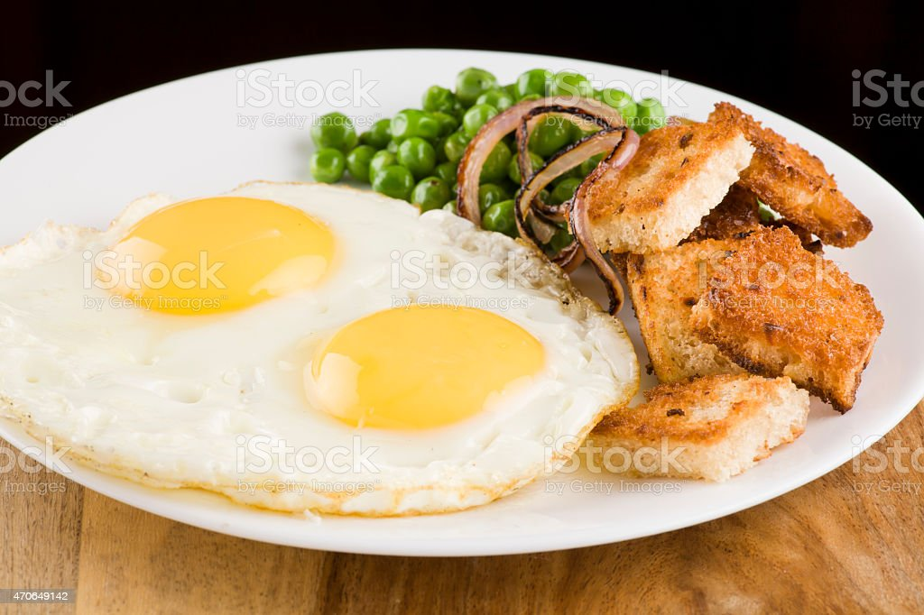 Fried eggs breakfast with peas onion and bread stock photo