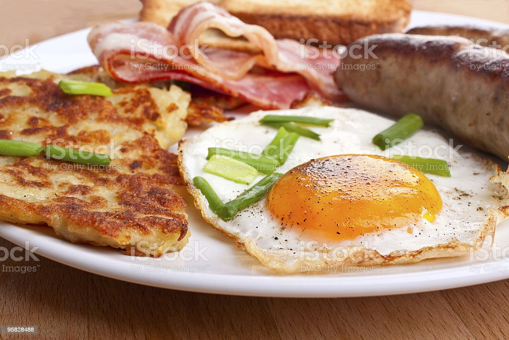 fried eggs, hash browns and bacon breakfast royalty-free stock photo
