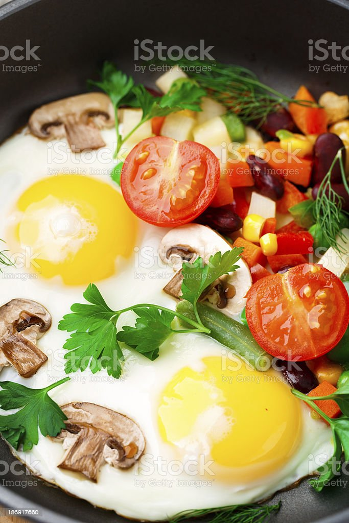 Fried eggs in a pan with vegetables royalty-free stock photo