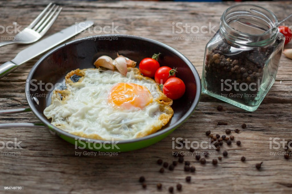 Fried eggs in pan with handle on wooden table royalty-free stock photo