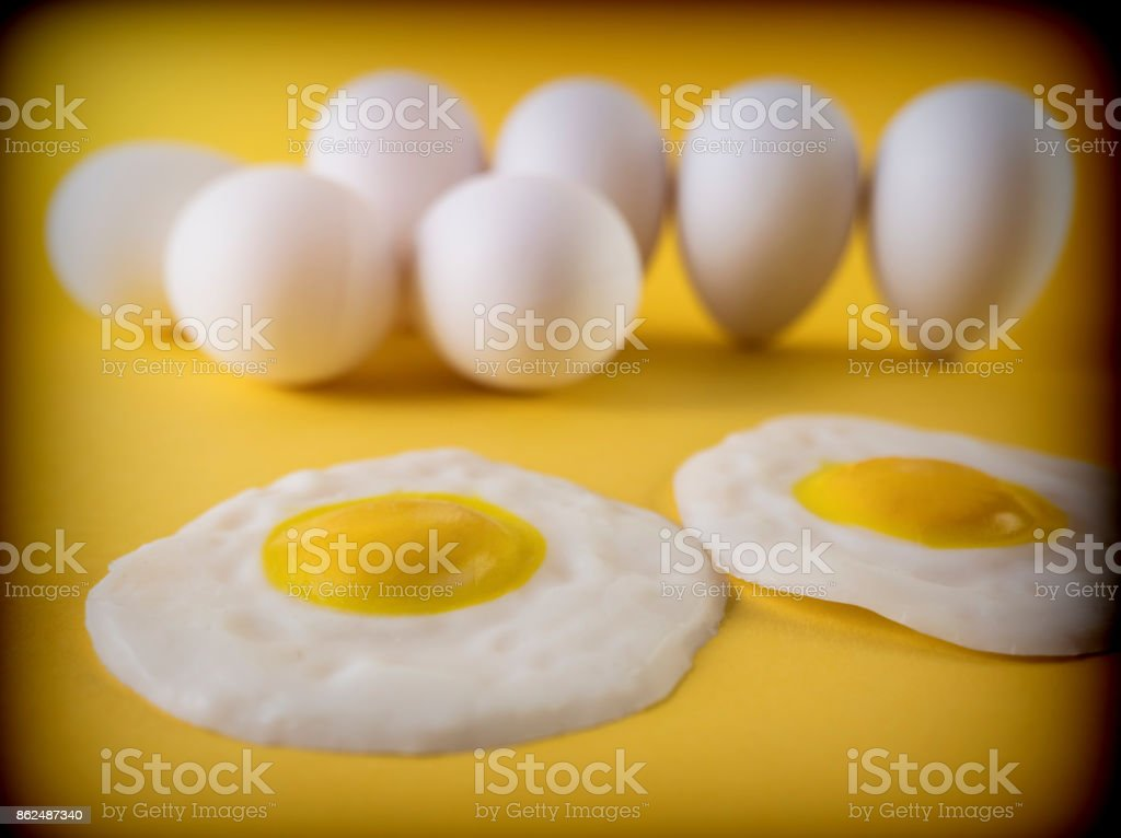 Fried eggs isolated on a yellow background stock photo