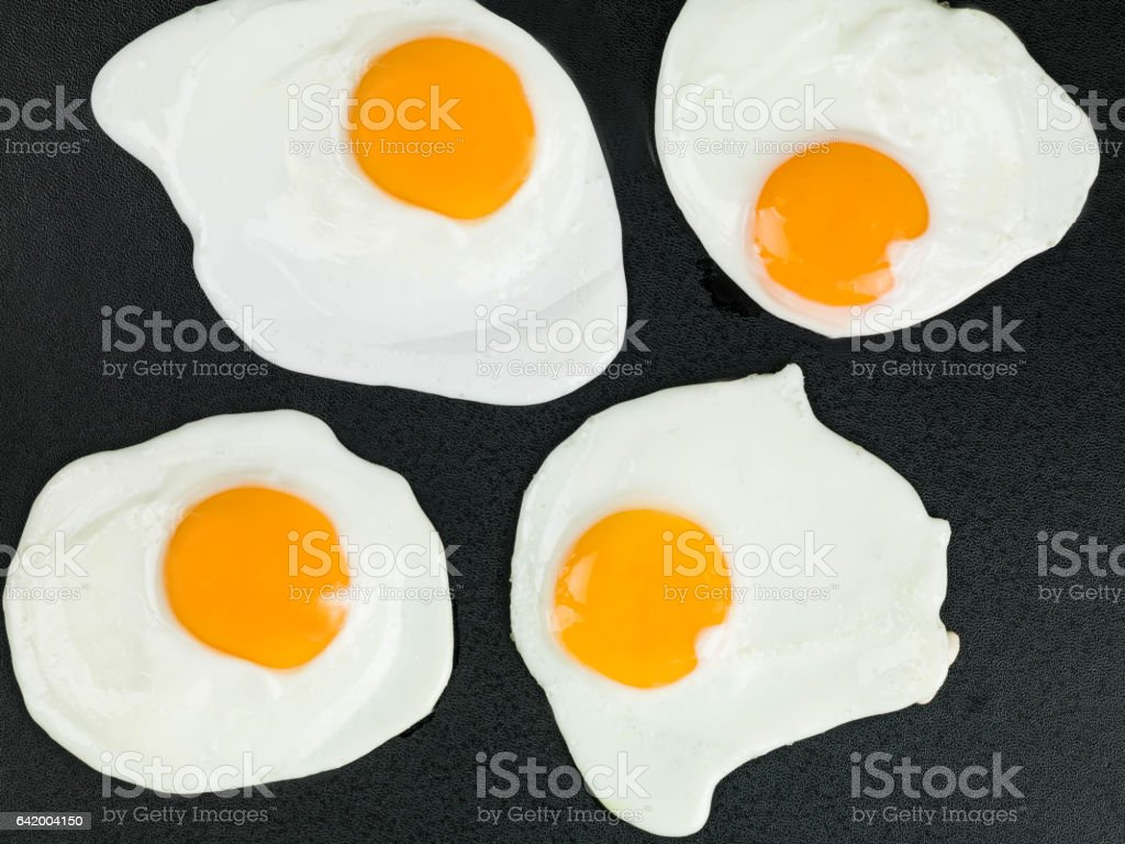 Fried Eggs on a Black Background stock photo