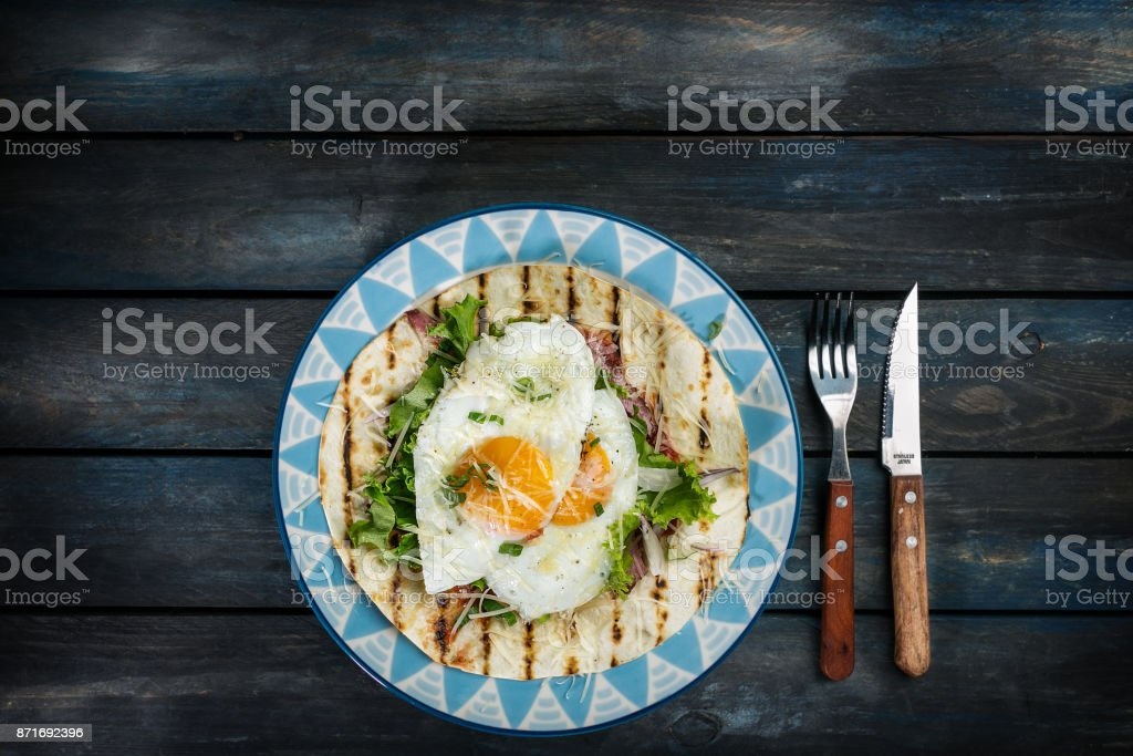Fried eggs on flour tortilla with green salad and cheese. Useful breakfast or lunch idea. Fork knife and beautiful dish on a colored wooden background. Top view stock photo