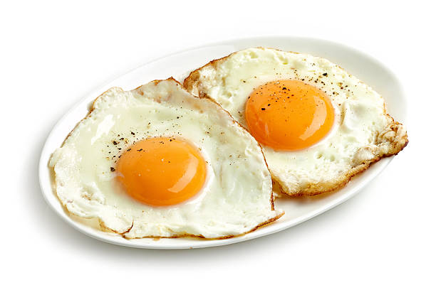 fried eggs on white background - fried egg stock photos and pictures