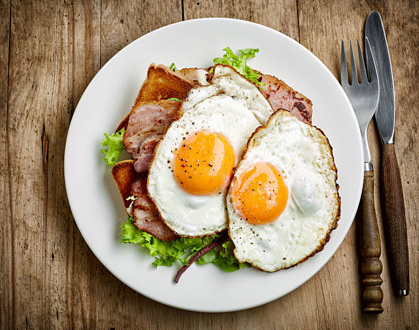 fried eggs on white plate - fried egg stock photos and pictures