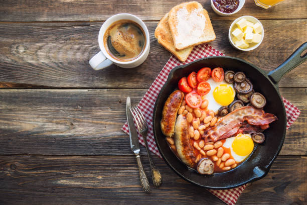fried eggs, sausages, bacon, beans and mushrooms in iron skillet, toasts, coffee, butter and jam on rustic wooden background - confiture tomatoes imagens e fotografias de stock