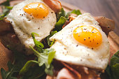 Fried eggs sunny side up on french baguette, ham and arugula