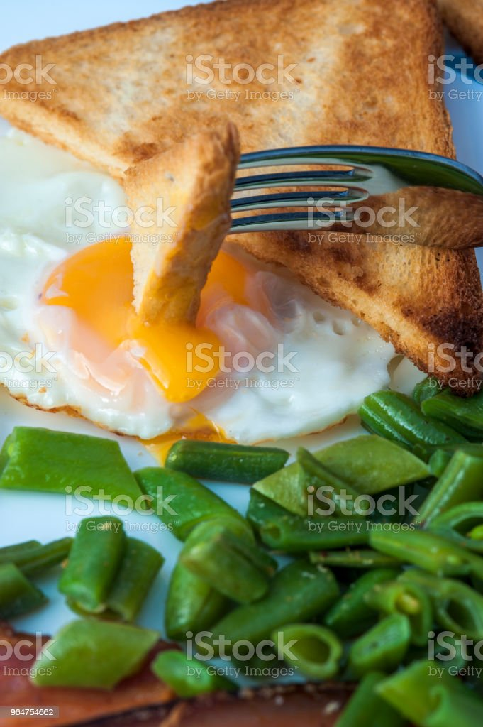 Fried eggs, toasts and bacon royalty-free stock photo