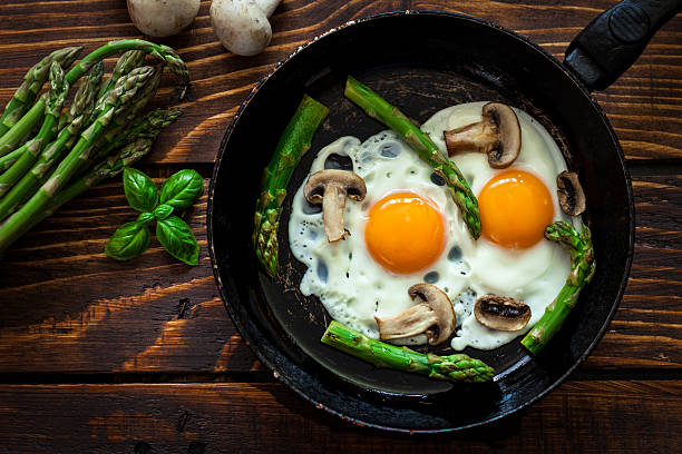 fried eggs with asparagus - fried egg stock photos and pictures