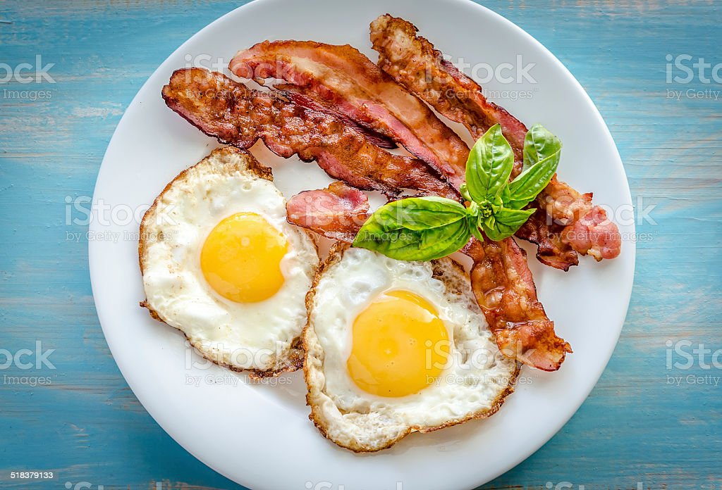 Fried eggs with bacon on the wooden table stock photo