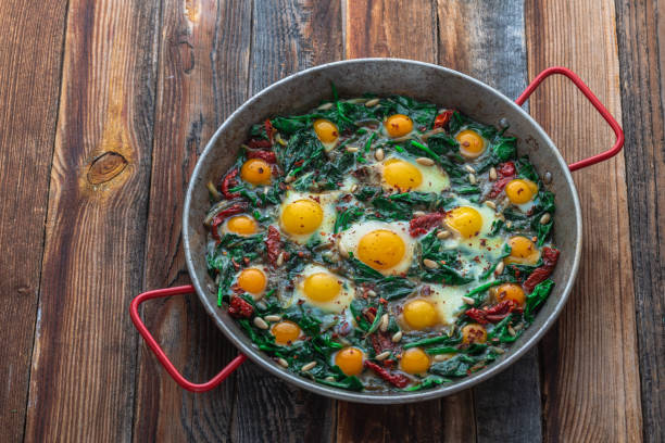 Fried eggs with spinach and pine nuts in iron skillet, copy space stock photo