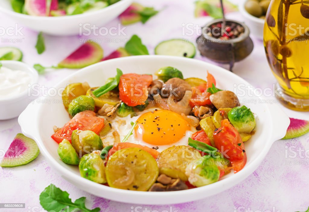 Fried eggs with vegetables - shakshuka and fresh cucumber, watermelon radish and arugula royalty free stockfoto
