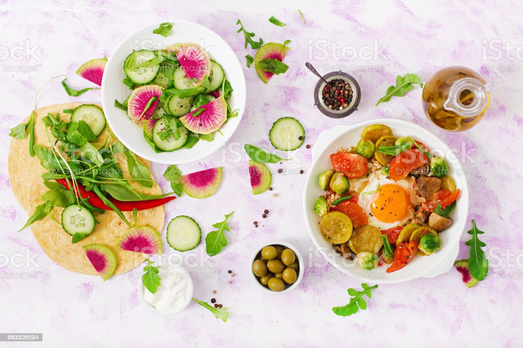 Fried eggs with vegetables - shakshuka and fresh salad cucumber, watermelon radish and arugula. Flat lay. Top view royalty-free stock photo