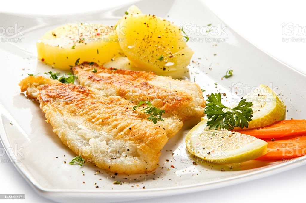 Fried fish and vegetables with garnished stock photo