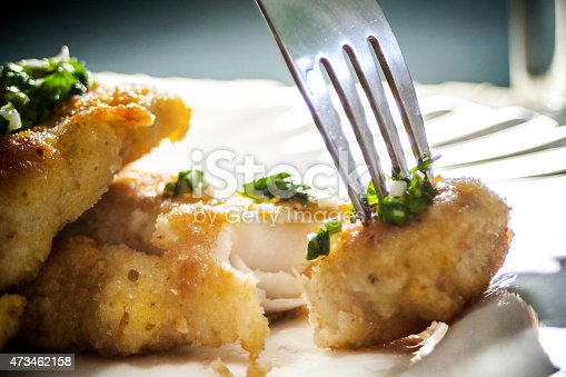 Taking a piece of fried fish fillet with a fork close up. Fish served with chopped parsley and garlic on white plate.