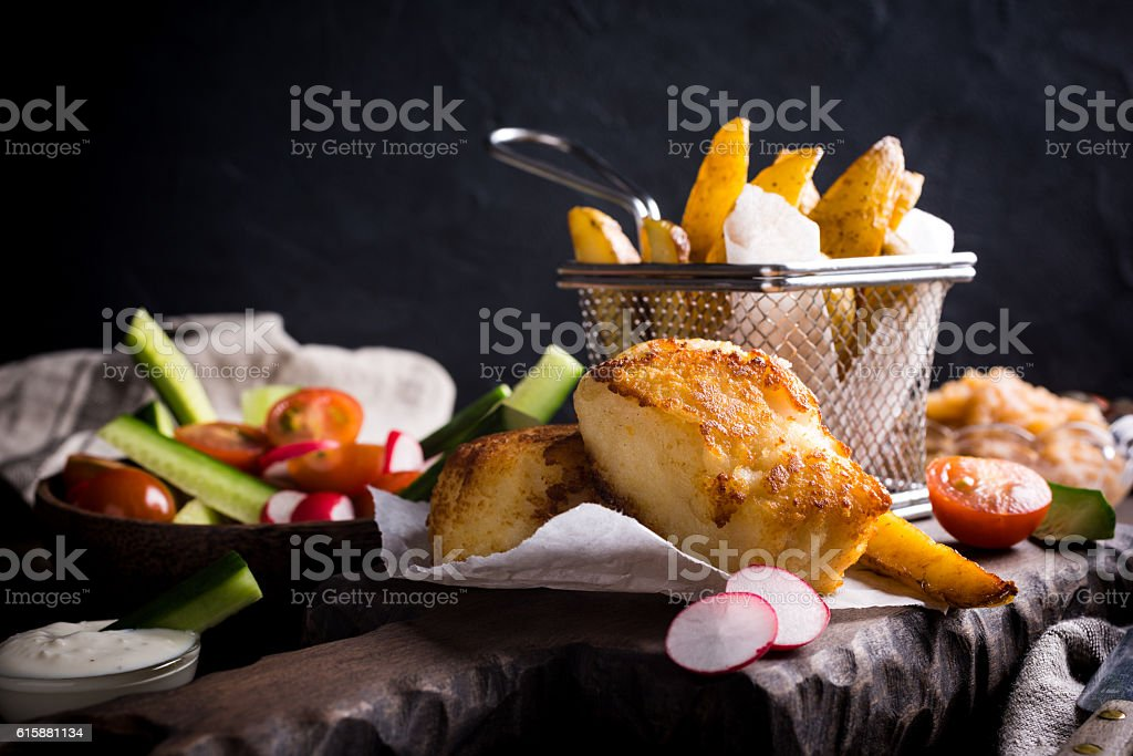 Fried fish fillet with baked potatoes stock photo