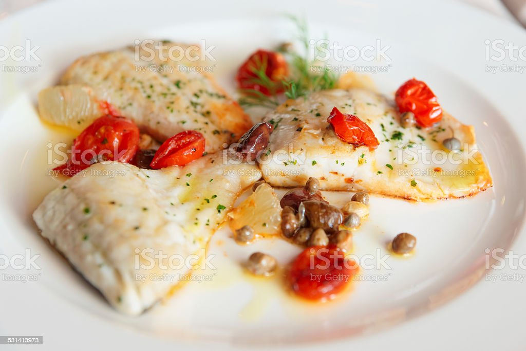 Fried fish fillet with capers and tomatoes stock photo