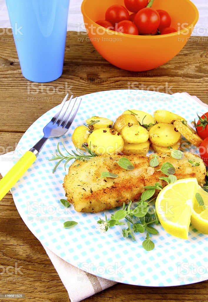 Fried fish fillet with rosemary potatoes and vegetables royalty-free stock photo