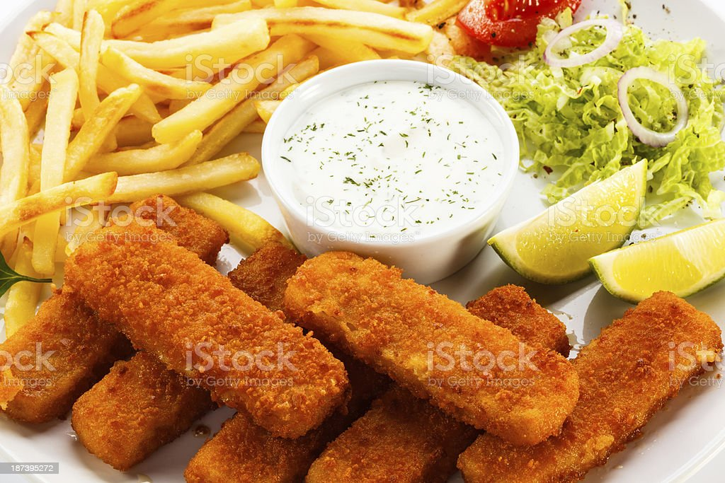 Fried fish fingers, French fries and vegetables stock photo
