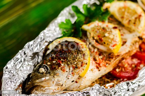 istock Fried fish in foil on a wooden background. 686222116