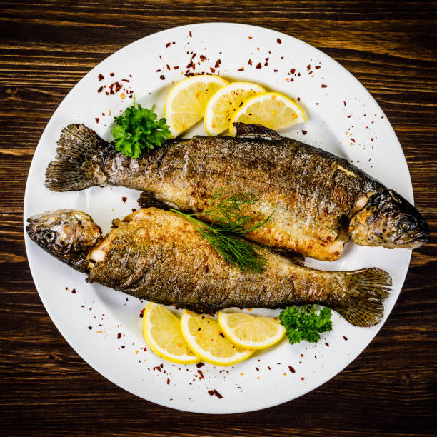 fried fish on white plate on wooden background - trout foto e immagini stock
