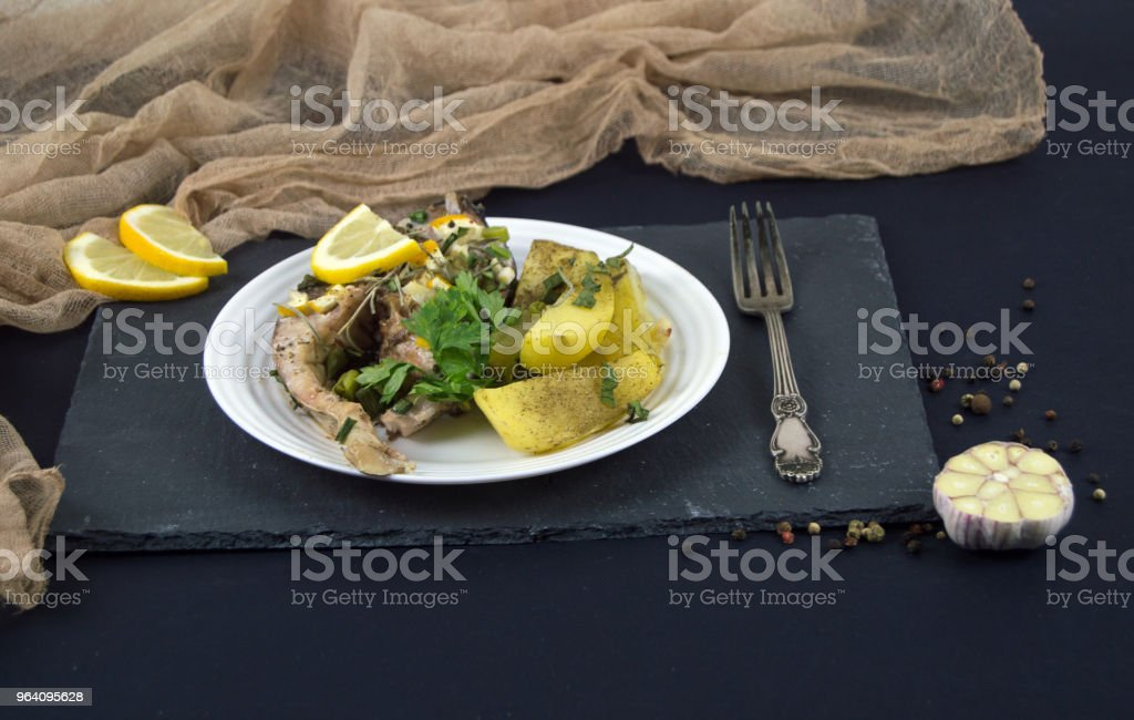 fried fish steak on a plate with potatoes, lemon, greens. Served lunch for healthy meal - Royalty-free Baked Stock Photo