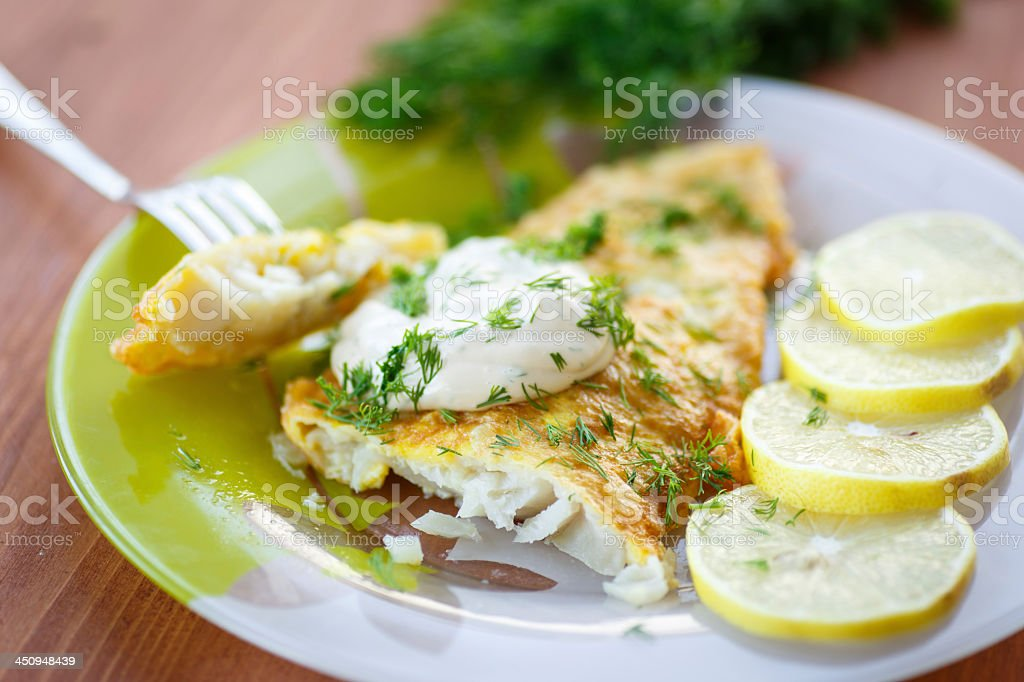 Fried fish with sliced lemons on the side stock photo