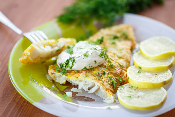 Fried fish with sliced lemons on the side fried fish with sauce and lemon on a plate perch fish stock pictures, royalty-free photos & images