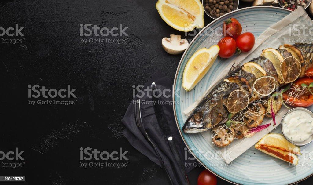 Gebratener Fisch mit Gemüse, serviert im Restaurant am schwarzen Tisch - Lizenzfrei Bildhintergrund Stock-Foto