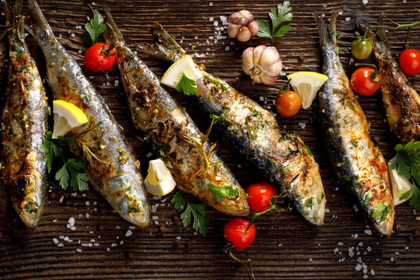gebratene fische mit zusatz von kräutern, gewürzen und zitronenscheiben auf einem hölzernen hintergrund. - marinade für grillfleisch stock-fotos und bilder