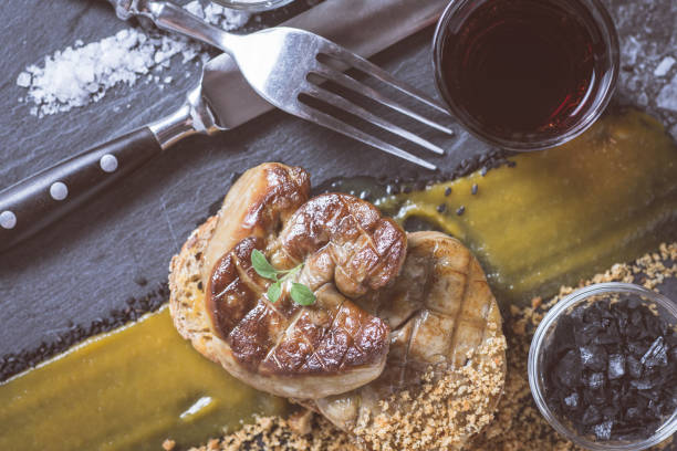 gebratene gänsestopfleber mit mangopüree auf dunklen stein hintergrund. französische küche-konzept. - gänsefett stock-fotos und bilder