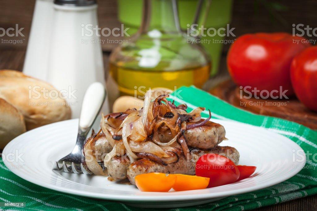 Fried gebratene weiße Wurst mit Zwiebeln auf die plate.white Würste in einer gusseisernen Pfanne. – Foto