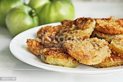 Plate of fresh fried green tomatoes. Tomatoes have been coated in cracker crumbs before frying. Extreme shallow depth of field with selective focus.