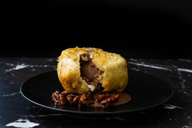 Sorvete frito com chocolate e nozes assadas em prato preto escuro. - foto de acervo