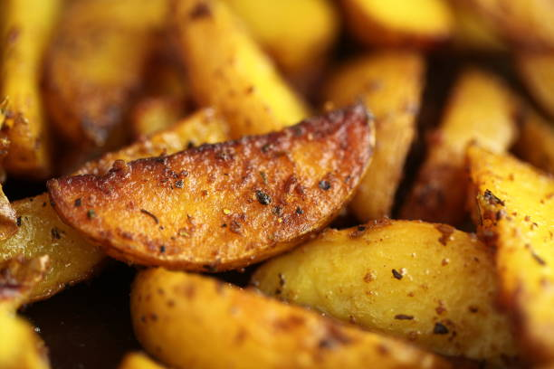 fried in ghee with spices pieces of potatoes stock photo