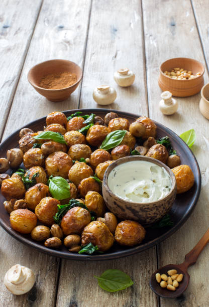 Fried little potatoes and mushrooms on clay plate on natural wooden background stock photo