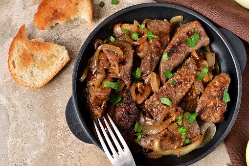 Fried liver with onions and apples on a concrete background