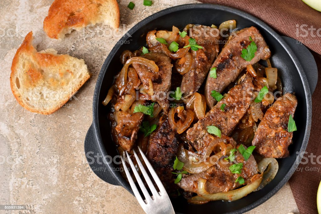 Fried liver with onions and apples on a concrete background stock photo