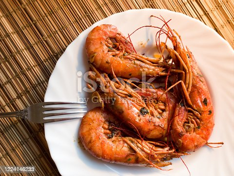 A lobster on a white plate, a straw lining under plate, fork, garlic