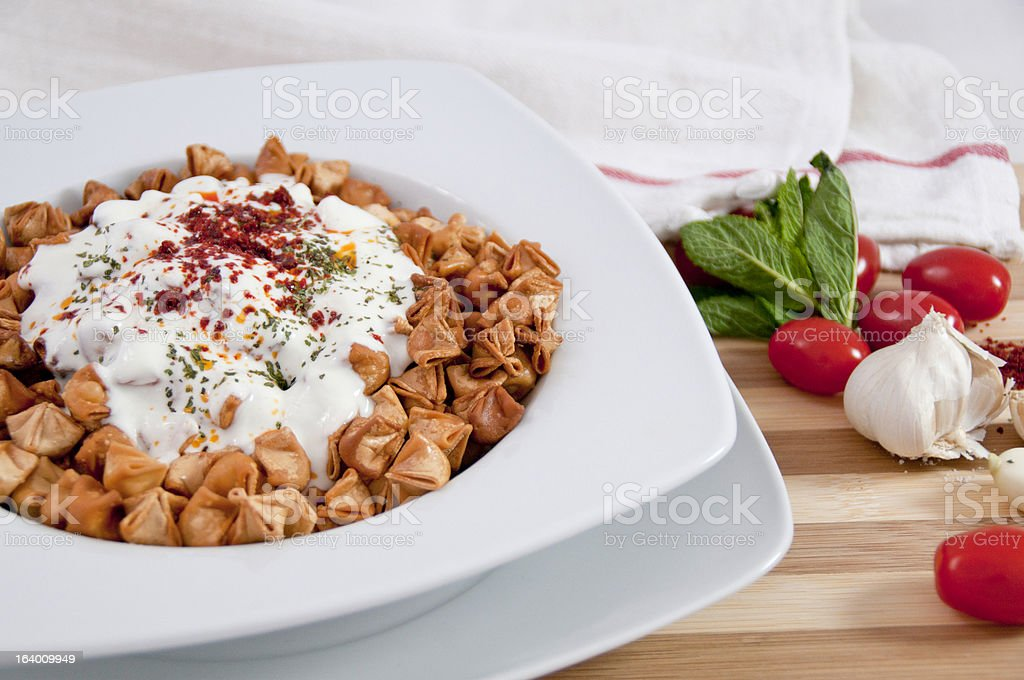Fried Manti served with yoghurt and tomato sauce royalty-free stock photo