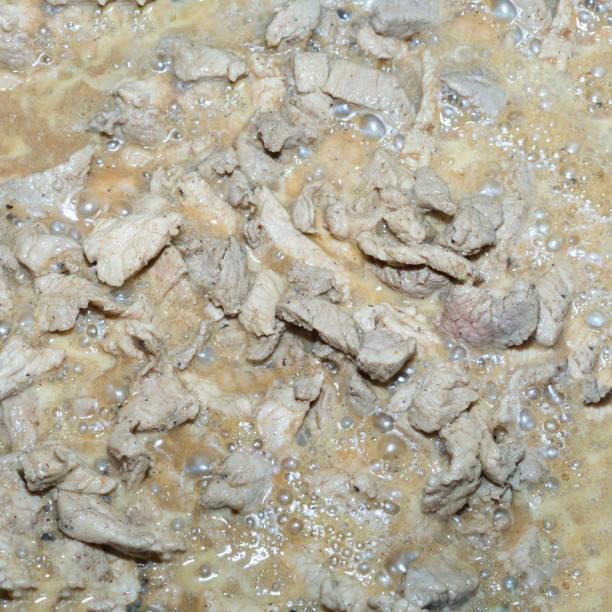 gebratene fleisch eine menge stücke brühe beige lichtmuster köstliche basisentwurf - schweinegulasch stock-fotos und bilder