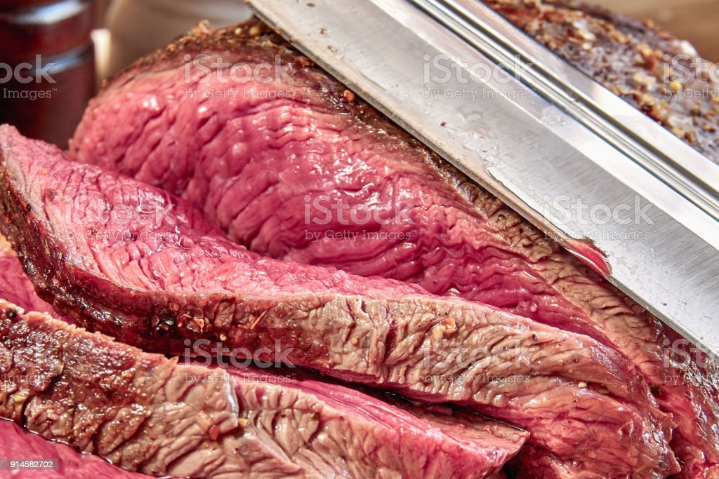 Fried meat with blood with hunting knife. Well done steak closeup. Rustic style. stock photo