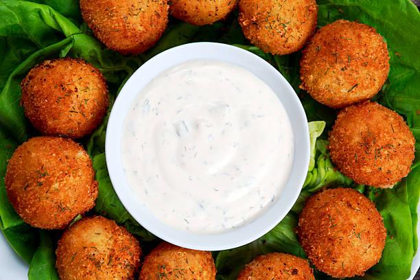 Fried mozzarella cheese stick balls with white sauce stock photo