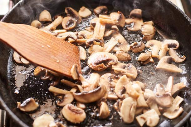 stekt svamp i en kastrull. matlagning svamp med ånga som härrör från dem. - frying pan bildbanksfoton och bilder