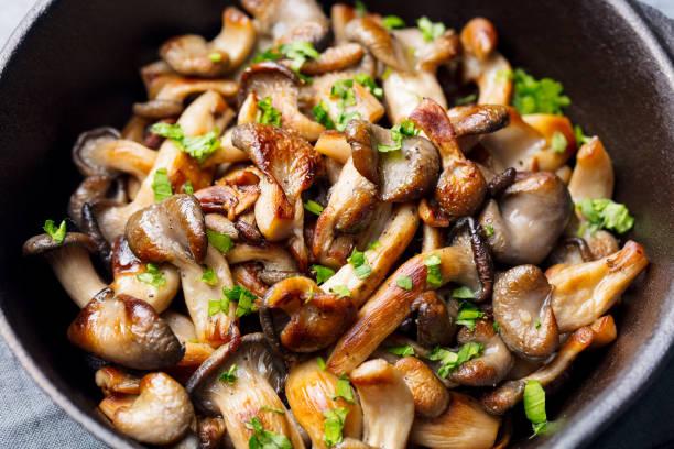 gebratene pilze mit frischen kräutern in schwarzem gusseisen pfanne. - pilzpfanne stock-fotos und bilder
