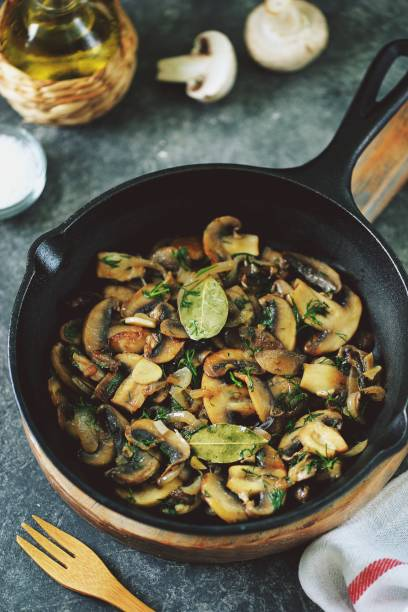 Fried mushrooms with onions, garlic, bay leaf and dill. stock photo
