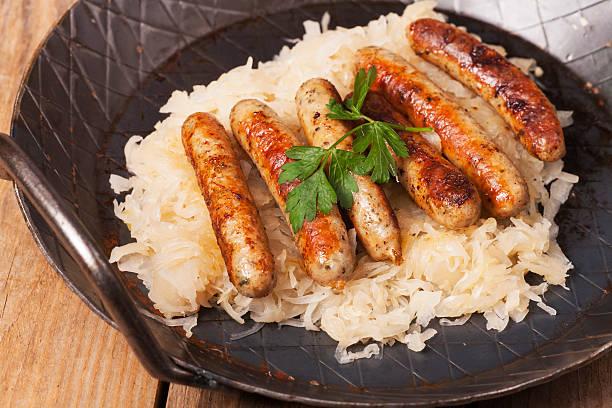 gebratene nürnberg würstchen - bratwurst mit sauerkraut stock-fotos und bilder