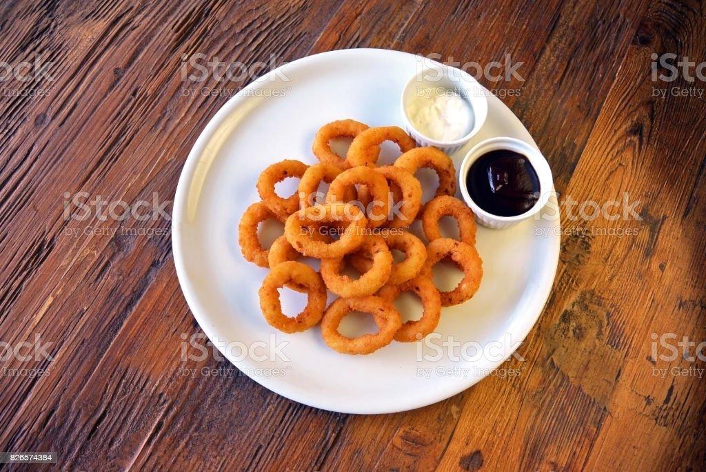 Anéis de cebola fritos e molhos na mesa de madeira - foto de acervo
