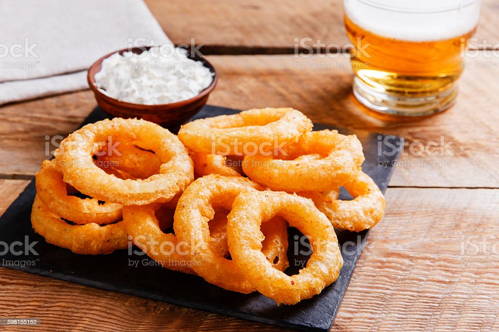 fried onion rings in batter with sauce stock photo