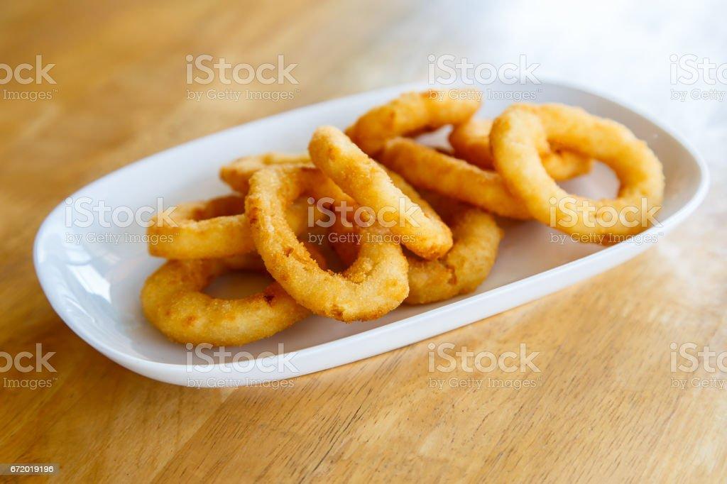 Anéis de cebola fritos em uma mesa de madeira - foto de acervo